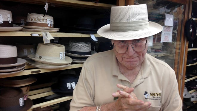 Sam Meyer, who turned 90 on August 6, 2014, designed five of the most popular hats sold at Meyer the Hatter, the family-owned CBD shop where he has worked since 1946. He is wearing a flattop straw hat that he designed.