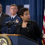 Attorney General Loretta Lynch, with Secretary of Agriculture Tom Vilsack, left, and U.S. Coast Guard Commandant Adm. Paul Zukunft, speaks Monday at the Department of Justice in Washington.