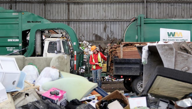 Waste Management trucks and customers unload waste garbage at the Olympic View Transfer Station in Bremerton. County commissioners are considering a fee increase for trash collection and disposal at its facilities.