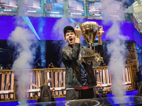 "Kyle Giersdorf celebrates as he holds up the trophy after winning the Fortnite World Cup solo finals Sunday in New York. Giersdorf, of Pottsgrove, Montgomery County, who goes by the name ""Bugha"" when competing, won $3 million as the first Fortnite World Cup solo champion."