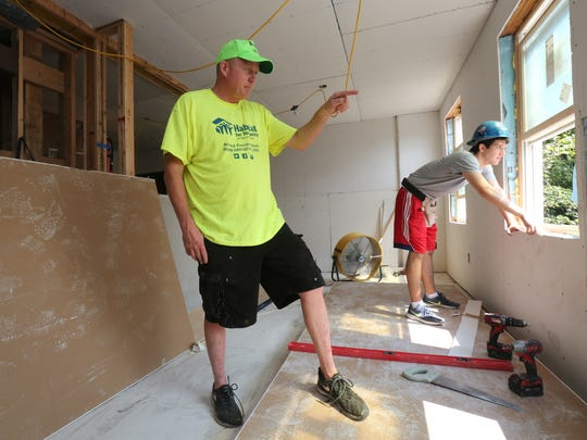 """Jim Killoran, the executive director of Habitat for Humanity Westchester, is pictured in a former """"crack house"""" under renovation on High Street in Yonkers, Aug. 10, 2017. Behind him is volunteer Ben Klestzick."""