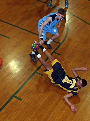 Justin Mitchell of Newburgh, playing for the Playmaker Academy, falls to floor after colliding with Mike DeMello of White Plains, playing for Frenji during e CYP Tournament game at Our Lady of Mercy Church in Port Chester March 25, 2014.