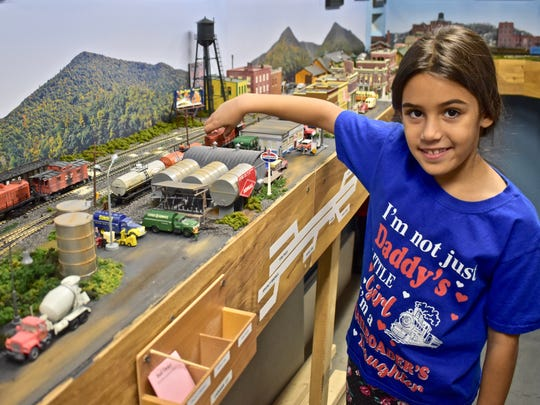 Dad's little helper, Madelyn Magill, works on the model train display.