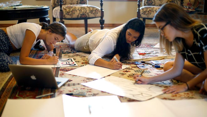 High Schoolers Karina Bratkov (left), 16, Leila Ismaio, 17, and Lauren Lawson, 17, make signs on Friday, July 8, 2016 for a Black Lives Matter protest in Springfield that is scheduled for Saturday.
