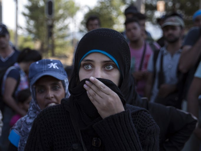 A young Syrian woman waits to cross the border with