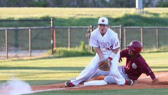 USJ third baseman Eli Brauss blocks a bad bounce Tuesday evening at St. George's runner steals third.
