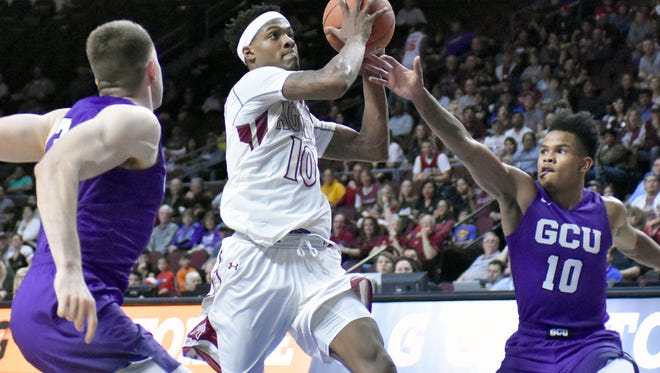 Jemerrio Jones splits two Grand Canyon University defenders as he goes in for a layup during Saturday's WAC Men's Basketball Championship game.