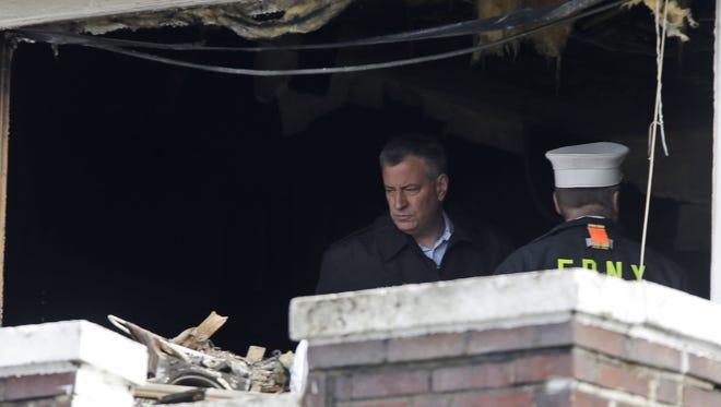 New York City Mayor Bill de Blasio tours the scene of a fatal fire in the Brooklyn borough of New York, Saturday.