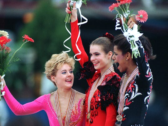 FILE- In this March 26, 1988, file photo, gold medalist Katarina Witt, of East Germany, is flanked by silver medalist Elizabeth Manley, left, of Canada and bronze medalist Debi Thomas, of the United States, during the medal ceremony at the World Figure Skating Championships in Budapest, Hungary. As the Olympics draws near, the sport of figure skating will once again be pumped into U.S. homes in primetime. But absent from the competition is the kind of rivalry that has elevated the sport over the years. (AP Photo/Dave Caulkin, File)