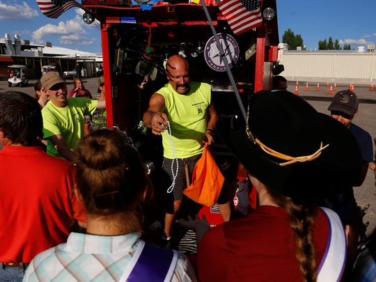 Kevin Mauzy representing the Bloomfield Fire Department hands out beads while riding in Squad 51 on Monday before the start of the San Juan County Fair Outhouse Race at McGee Park in Farmington.