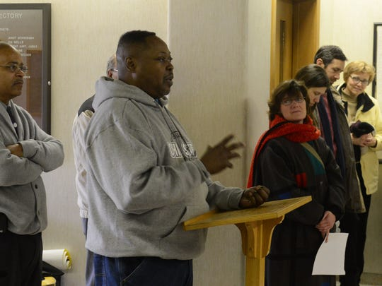 The Rev. C.J. Burel of Ebenezer C.O.G.I.C. leads with a prayer Monday during a service honoring Martin Luther King Jr.