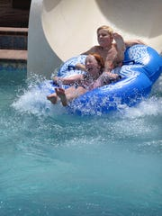 Olivia Taneda, 9, and her brother, Donovan Taneda, 10, fly out of the Cyclone water slide at Castaway Cove Waterpark Friday afternoon.