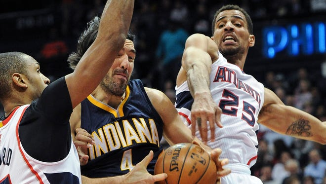 Indiana Pacers forward Luis Scola (4), of Argentina, fights for a rebound with Atlanta Hawks guard Thabo Sefolosha, right, and center Al Horford, during the first half of an NBA basketball game, Wednesday, Jan. 21, 2015, in Atlanta. Atlanta won 110-91. (AP Photo/John Amis)