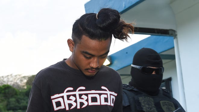 Kelly Hutch Apenis, 18, is escorted at the Guam Police Department Hagåtña Precinct on Dec. 30, 2017. Apenis was arrested for his role in a strong-arm robbery at the Micronesia Mall on Dec. 23.