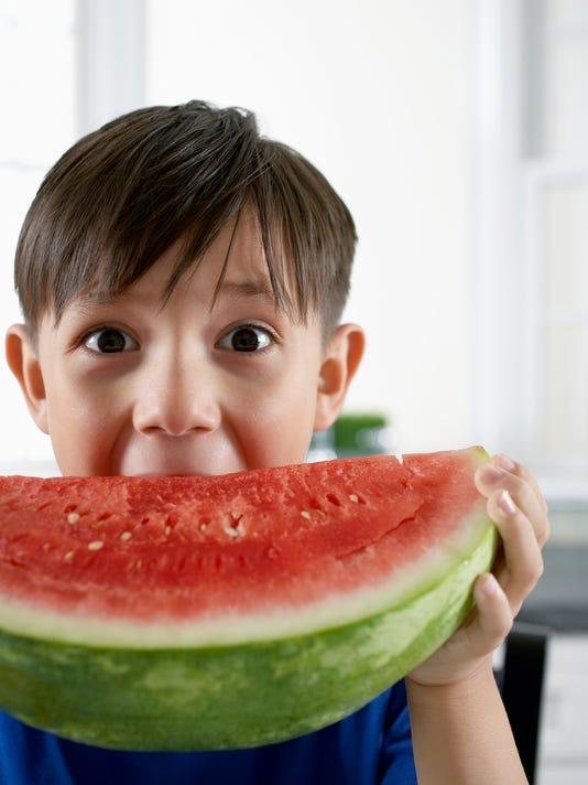 Boy (6-8) eating watermelon, close-up