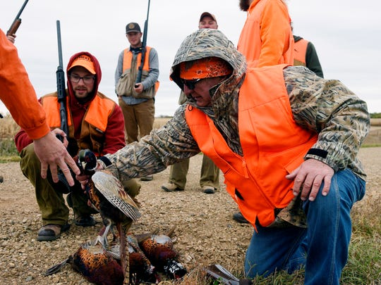 Kurt Anderson (right) stacks the pheasants shot by