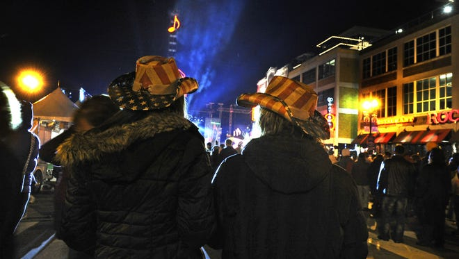 Lisa Kurczka, left, and Jessica Kemper wear American Flag cowboy hats as they celebrate New Year's Eve in downtown Nashville.