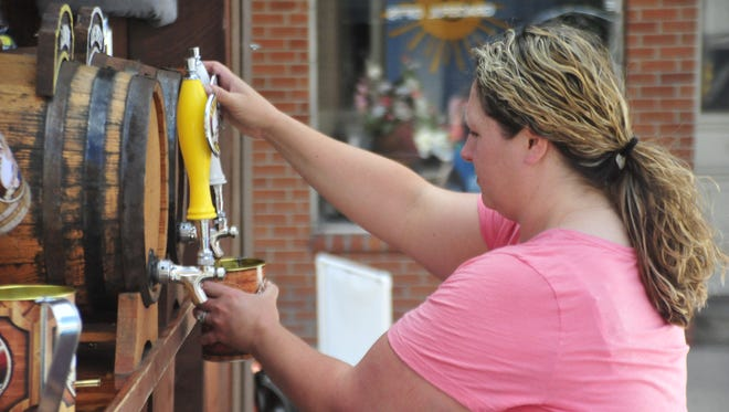Amy Safford of Bucyrus pours a cool glass of tea Friday at the Bucyrus Bratwurst Festival.