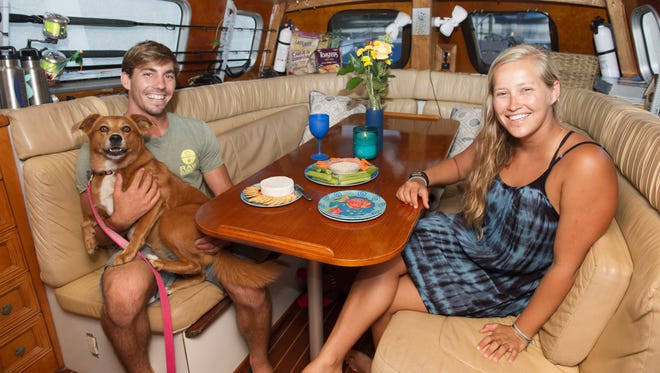 """""""We feel blessed to be able to live such a great life aboard Adrenaline and make a living doing what we love,"""" says Billy Swezey, holding Jetty, with girlfriend Sierra Groth."""