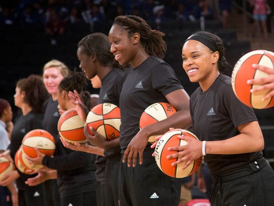 """Members of the New York Liberty basketball team await the start of a game against the Atlanta Dream, Wednesday, July 13, 2016 in New York. Between the Black Lives Matter movement, the Orlando shooting and the LGBT community, more WNBA players have been taking active roles in expressing their views on social issues. In the midst of """"Camp Day"""" at the New York Liberty's mid-morning game Wednesday, Liberty players stood in solidarity as they donned all-black warmups in support of the Black Lives Matter movement. (AP Photo/Mark Lennihan)"""