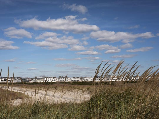 In this Oct. 26, 2016 photo, beach grass is now growing on top of a dune constructed to protect the homes in the Breezy Point neighborhood in the Queens borough of New York. People have worked hard, and mostly successfully, over the past four years to restore the New York and New Jersey coastline to what it was before Superstorm Sandy crashed ashore. But some areas have not recovered, nor will they ever from the Oct. 29, 2012, storm. (AP Photo/Mark Lennihan)