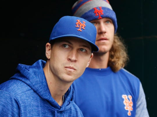 New York Mets pitchers Jacob deGrom, left, and Noah Syndergaard watch from the dugout in the seventh inning of a baseball game against the Philadelphia Phillies, Sunday, Sept. 9, 2018, in New York. The Mets had scheduled deGrom to start but he was scratched. (AP Photo/Mark Lennihan)