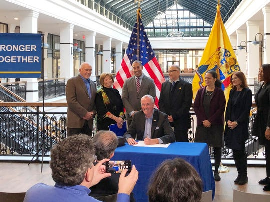 Democratic Gov. Phil Murphy signs an executive order creating a board to look into setting up a state-run bank, alongside labor and other supporters, Wednesday in Newark, N.J.