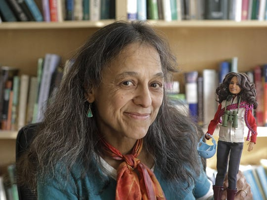 "This Dec. 3, 2019, photo, ecologist Nalini Nadkarni is shown in her lab on the University of Utah campus in Salt Lake City holding a Barbie created to look like her when she's climbing into the treetops to study the rainforest canopy. Nadkarni's childhood climbing trees shaped her career and now she's hoping she can get help kids interested in science in an new way: Barbies. Nadkarni has long created her own ""treetop Barbies"" and has now helped Mattel and National Geographic create a line of dolls with careers in science and conservation. (AP Photo/Rick Bowmer)"