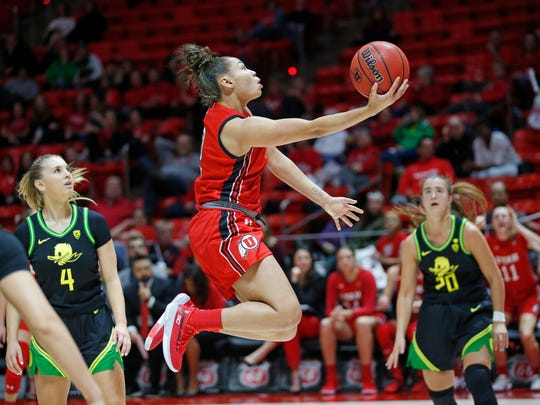 Utah guard Kiana Moore (0) lays the ball up as Oregon's Jaz Shelley (4) and Sabrina Ionescu (20) watch during the third quarter of an NCAA college basketball game Thursday, Jan. 30, 2020, in Salt Lake City. (AP Photo/Rick Bowmer)