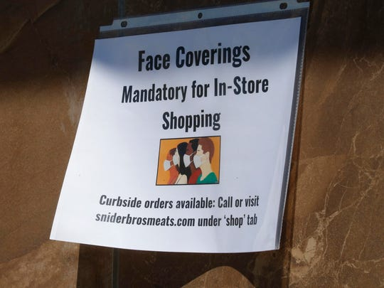 """A sign indicating face masks required is shown at Snider Bros. Meats in Holladay, Utah. Gov. Gary Herbert says he has no plans to shut down the economy and appears unwilling to make face masks mandatory despite warnings from the state's epidemiologist that a """"complete shutdown"""" might be imminent if Utah can't stop a prolonged spike of coronavirus cases."""