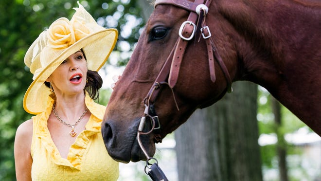 "Tanyell Dell'Oso pets ""Bob"" an outrider's horse, as she poses in a butter yellow hat purchased at That's Hats in Chadds Ford with a yellow textured dress with a ruffled de'collete' neckline near the paddocks at Delaware Park on Wednesday afternoon."
