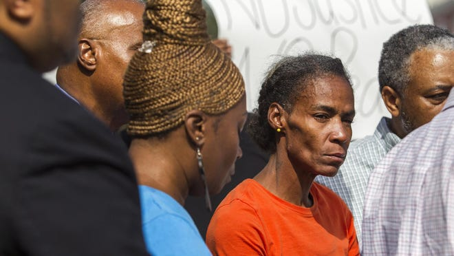 Phyllis McDole, mother of Jeremy McDole – shown as she watches Pastor Ty Johnson talk to media Thursday outside her home in the 100 block of N. Rodney St. She has been charged with assaulting a woman she believed told police in a 911 call that her son was armed and had shot himself.