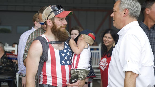 N.C. Lt. Gov. Dan Forest, right, speaks with Haywood County resident Austin Reece, left, holding his two sons, during the Independence Day campaign event for Forest and N.C. District 11 Congressional Republican candidate Madison Cawthorn Saturday at Grandad's Apples N' Such.
