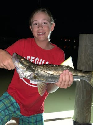 Ryann Quinn shows a snook she caught using live shrimp in the Palm Coast canals.