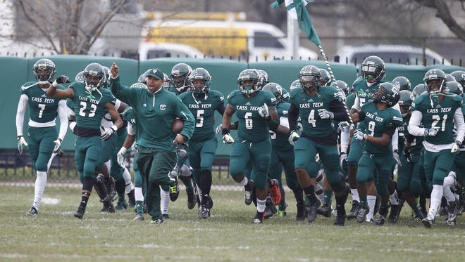 Detroit Cass Tech coach Thomas Wilcher leads his team out for their regional semifinal game against Macomb Dakota in Detroit on Nov. 16, 2013.