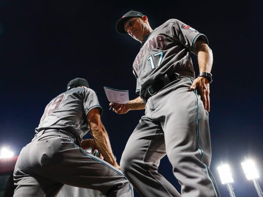 Arizona Diamondbacks manager Torey Lovullo (17) walks back into the dugout in the seventh inning of the team's baseball game against the Cincinnati Reds, Tuesday, July 18, 2017, in Cincinnati. (AP Photo/John Minchillo)
