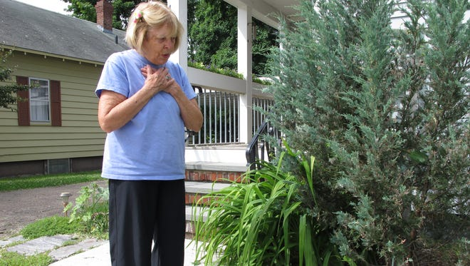 Diana Carlisle stands beside a bare spot in her garden where a prize lily once stood next to her driveway on Lakeview Terrace in Burlington. Photographed on Tuesday, June 21, 2016.