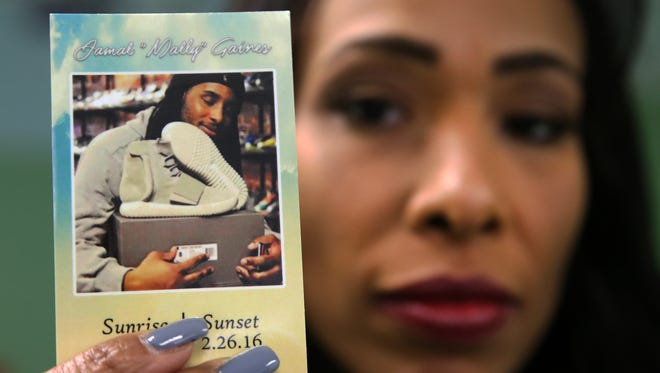 """Tina Wilson holds a photo of her son, Jamal """"Mally"""" Gaines, 21, owner of East Coast Boutique, a sneaker store at 1546 Irving St. in Rahway. Gaines was shot inside his store on Feb. 26, 2016 and died at the scene."""