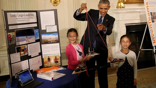WASHINGTON, DC - APRIL 13:  U.S. President Barack Obama listens to sisters Kimberly Yeung (R) and Rebecca Yeung (L) explain their science project while touring exhibits at the White House Science Fair April 13, 2016 in Washington, DC. The Yeung sisters, from Seattle, Washington, built a homemade spacecraft out of archery arrows and wood scraps, and launched it into the stratosphere via a helium balloon. They named it the Loki Lego Launcher after their late cat and a Lego figurine, and it records location coordinates, temperature, velocity, and pressure and reports the data back to the young inventors on the ground.  (Photo by Win McNamee/Getty Images)