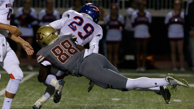 Oak Christian's Michael Owusu (88) brings down Westlake High's Nathan Brooks (29) during Friday's Marmonte League game. Both teams qualified for the playoffs. League champion Oaks Christian hosts La Habra while Westlake travels to Arroyo Grande.