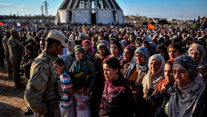 A picture taken on Oct. 14, 2017 in the Kurdish town of Kobane in northern Syria shows people gathering and mourning during the funeral of a Kurdish fighter, who was killed in clashes against Islamic State fighters in the city of Deir Ezzor.