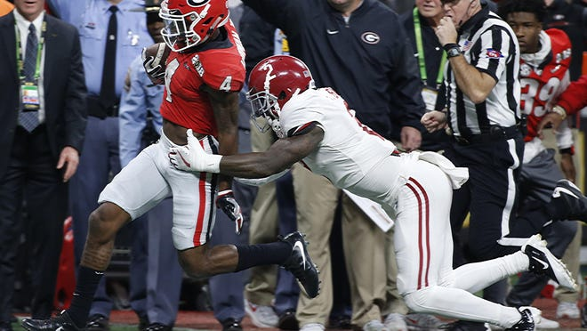 Georgia wide receiver Mecole Hardman (4) breaks a tackle from Alabama defensive back Tony Brown (2) during the NCAA Championship game in Atlanta on Jan. 8, 2018.