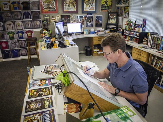 Paws, Inc. artist Jeff Wesley works at his desk in Albany.