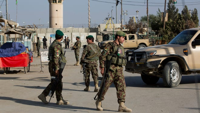 Afghan soldiers guard the main road to the Bagram Airfield's main gate in Bagram, north of Kabul on Nov. 12, 2016. An explosion at the U.S. airfield in Afghanistan early Saturday killed four people, said the head of international forces in the country.