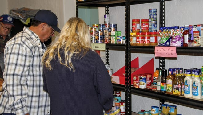 Residents shop at the Our Lady of the Light Catholic Church food pantry Tuesday. The church was giving away 150 turkeys.