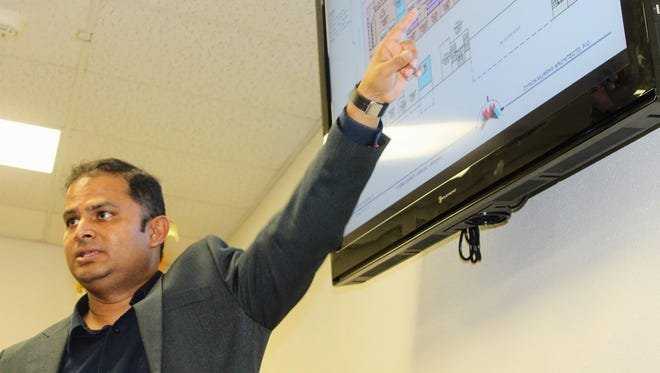 Dyron Murphy Architects Project Manager Nitish Suvarna shows a blueprint design for the 12th Judicial District Courthouse, 1000 New York Ave. at the county commission's special meeting Wednesday.