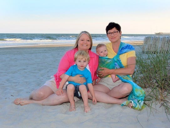 Lisa and Julia Tate-Keith hold their sons, Luke, left,