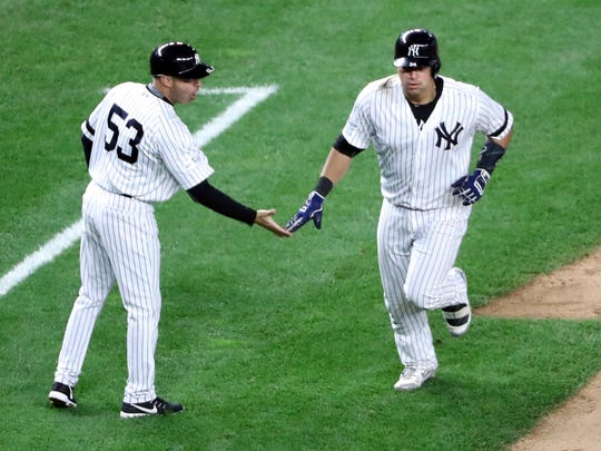 New York Yankees catcher Gary Sanchez (24) celebrates with third base coach Joe Espada (53) after hitting a home run during the ALCS