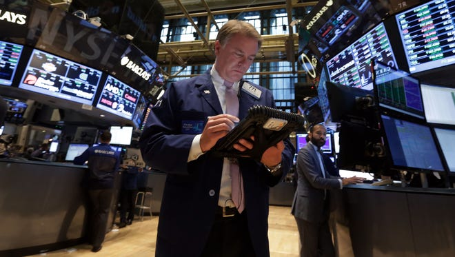 In this Sept. 18, 2013, file photo trader F. Hill Creekmore works on the floor of the New York Stock Exchange.