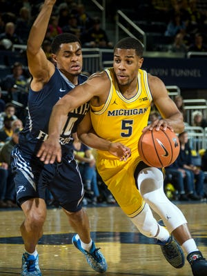 North Florida guard Osborn Blount, left, defends Michigan guard Jaaron Simmons (5) in the first half of U-M's 86-66 win on Saturday, Nov. 11, 2017, at Crisler Center.